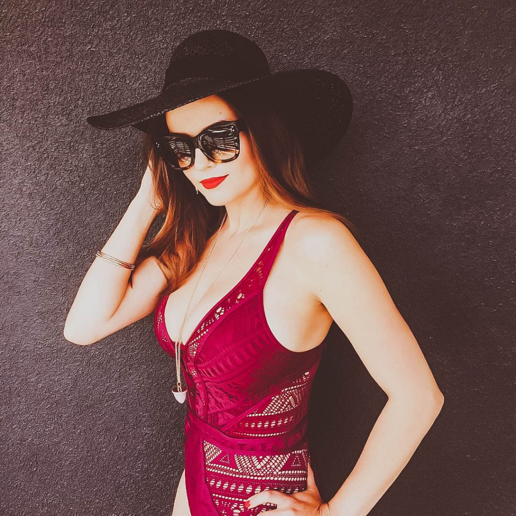 Irina Bond, BECCA burgundy Show & Tell openwork crochet cutout one-piece swimsuit, H&M black floppy hat, Celine sunglasses
