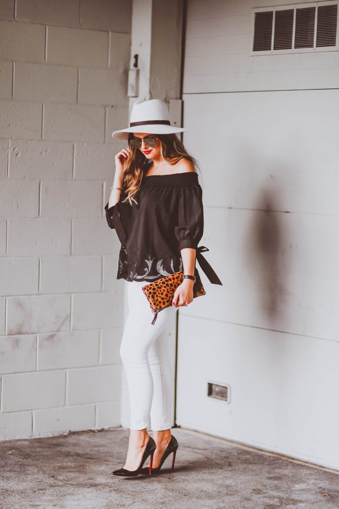 black off-the-shoulder cutout top, white distressed skinny jeans, janessa leone camellia white fedora, daniel wellington watch, clare v leopard foldover clutch, christian louboutin black patent pigalle pumps, le specs prince sunglasses